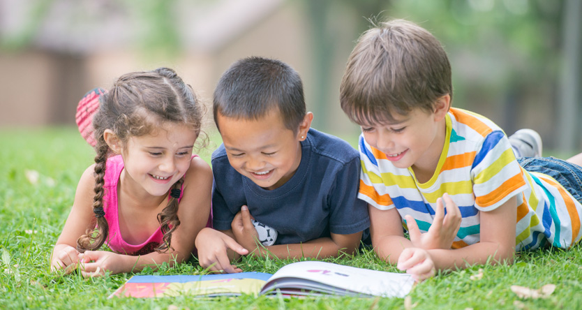Children reading in grass