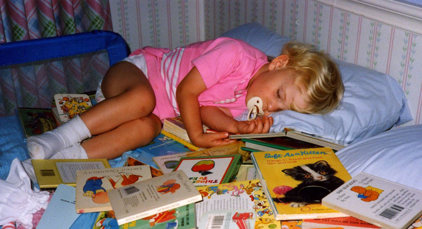 child sleeping in books